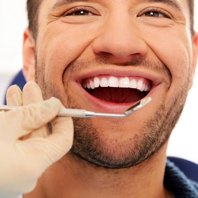 """""""Happy man doing teeth checkup at dentist's surgery"""" stock image"""
