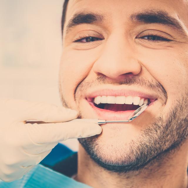 """Handsome smiling man at doing checkup at dentist's surgery"" stock image"