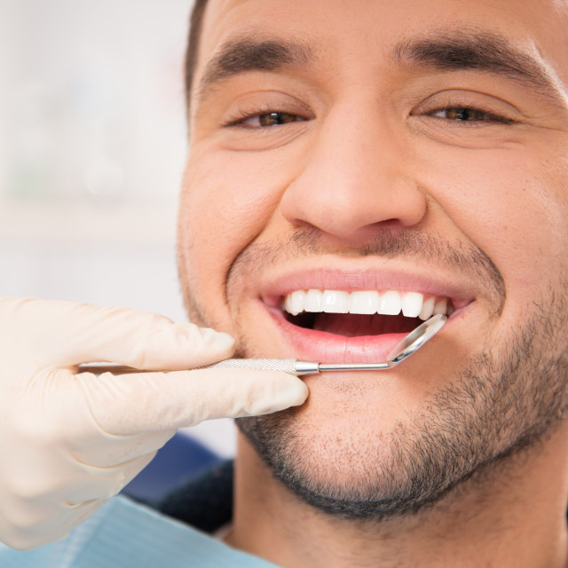 """Handsome smiling man at doing checkup at dentist's surgery"" stock image"