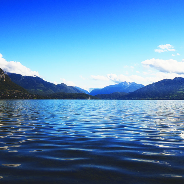 """A Calm Lake Annecy framed by mountains"" stock image"