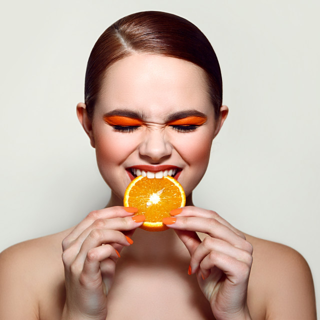 """Sour orange. The girl is tasting the fruit."" stock image"