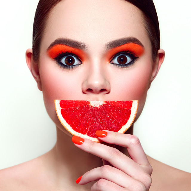 """Red grapefruit. Girl holding fruit in her hand in the face."" stock image"
