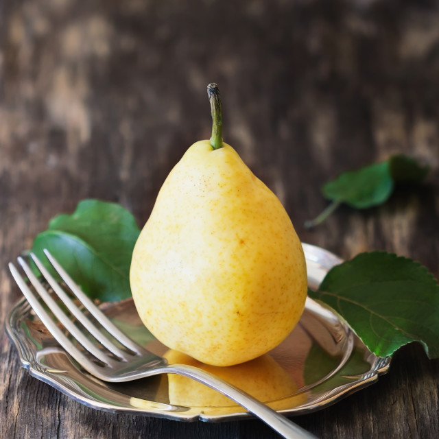 """Organic ripe pear in vintage plate"" stock image"