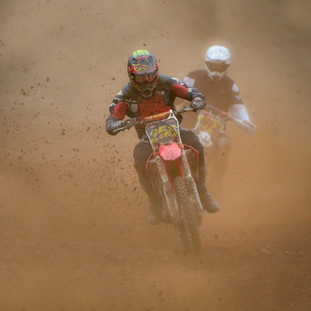 """Motocross riders in the dust"" stock image"
