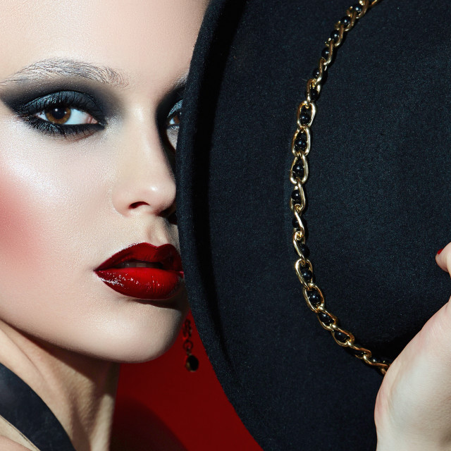 """""""Rock girl in a black hat with red lips and dark eyes."""" stock image"""
