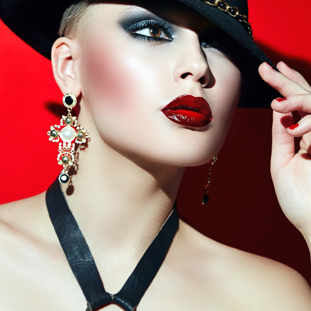 """""""Rock girl in a black hat with red lips and dark eyes in a corset."""" stock image"""