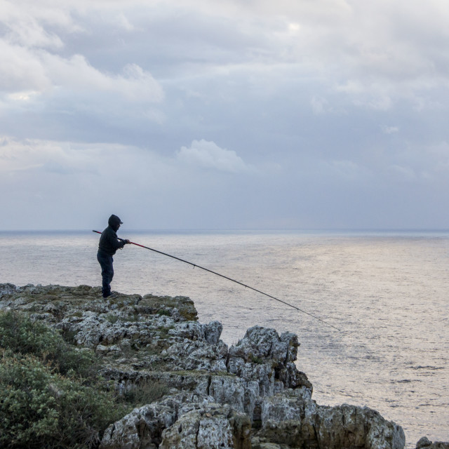 """Fisherman at a cliff"" stock image"