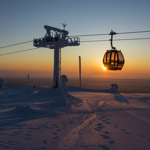 """Cable Car passes the setting sun. Yllas, Finland"" stock image"
