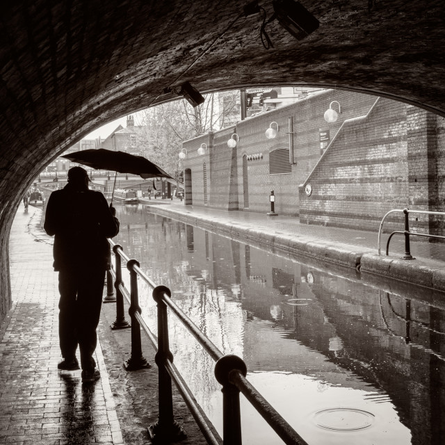 """A Man with an Umbrella in a Canal Scene"" stock image"