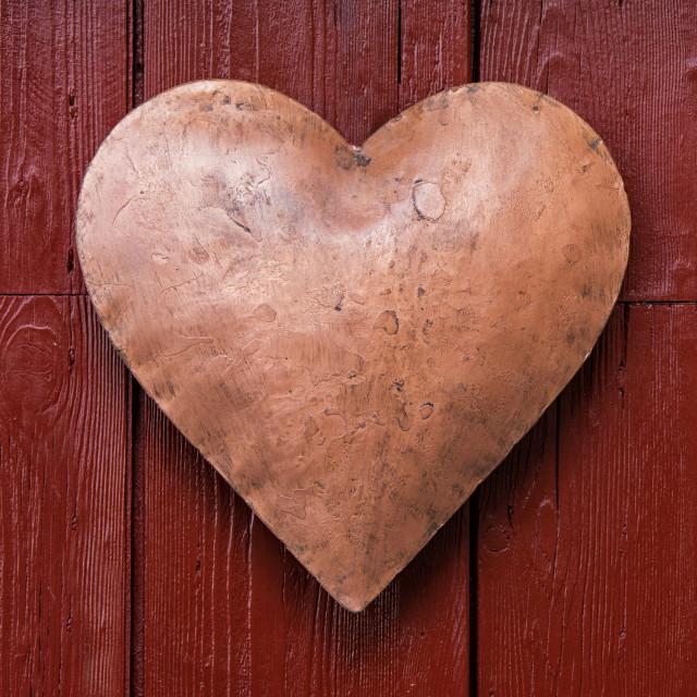 """Metal heart hanging from a red wooden door"" stock image"