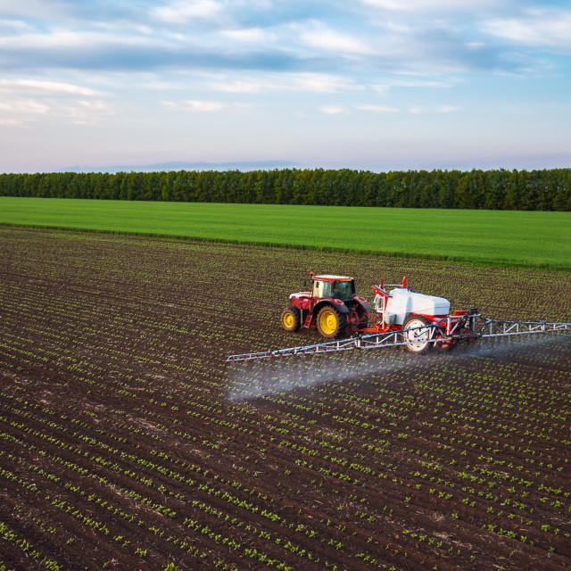 """Farming tractor spraying on field at spring"" stock image"