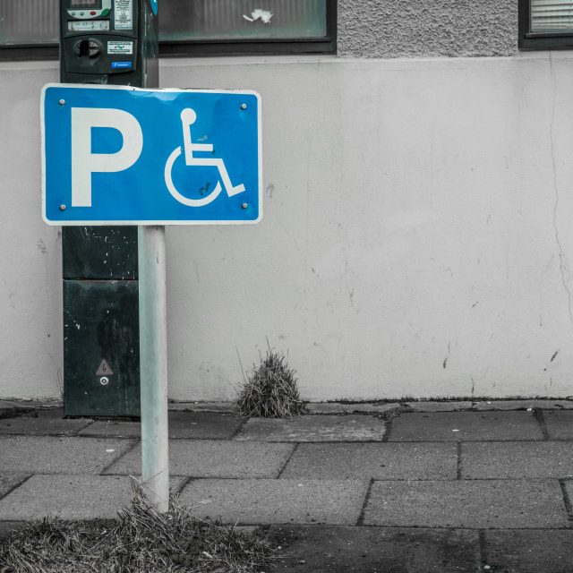"""Handicap parking sign on a street"" stock image"