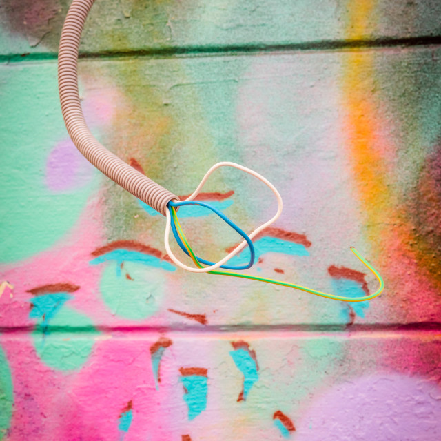 """Wires coming out of a grungy wall with grafitti"" stock image"
