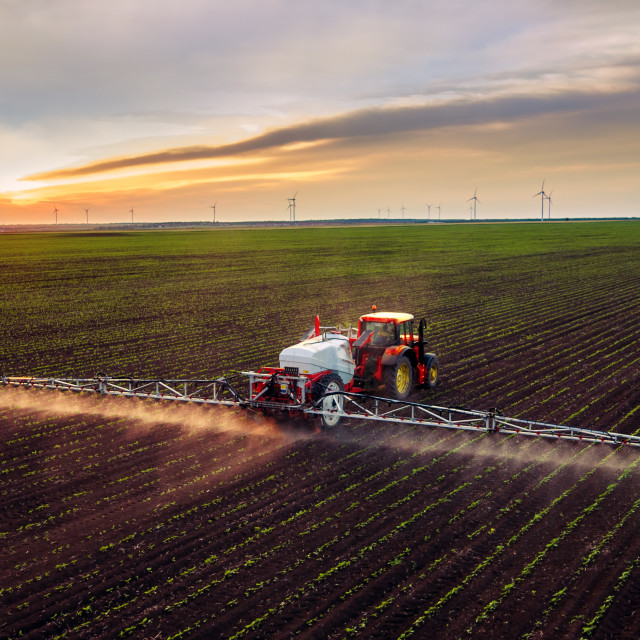 """Tractor spraying field at spring"" stock image"