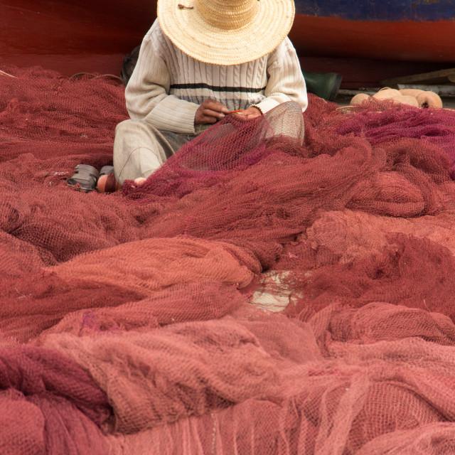 """Fisherman repairing his net, Port of Essaouira, Morocco"" stock image"