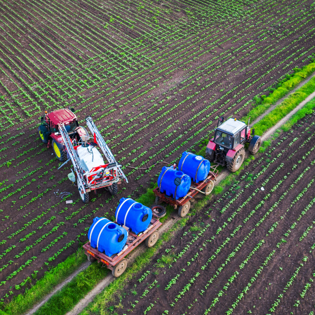 """Tractor spraying field at spring,aerial view"" stock image"