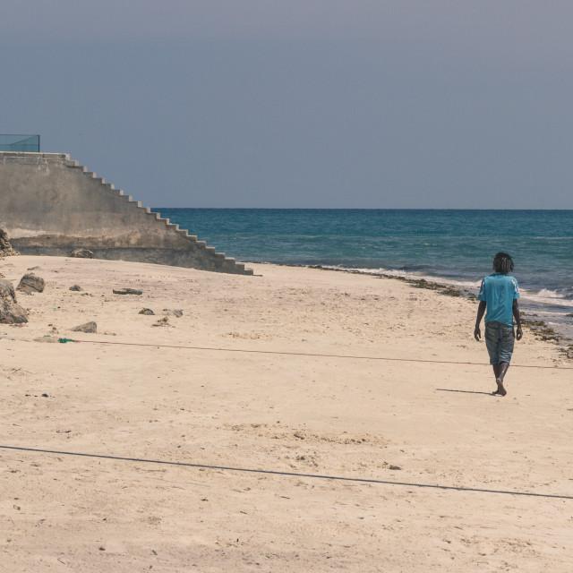 """Man with dreadlocks walks on Zanzibar beach"" stock image"