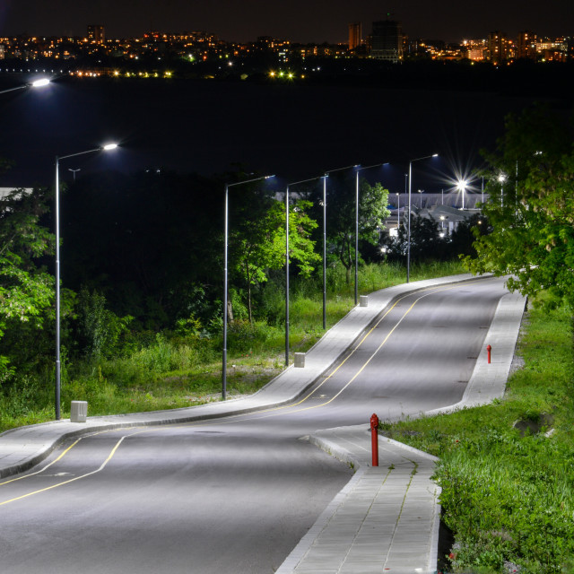 """Photo of road at night leading to a small fishing port and back to see the city lights"" stock image"
