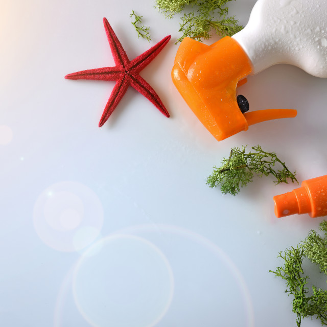 """Two sunscreen spray with starfish on glass table top"" stock image"