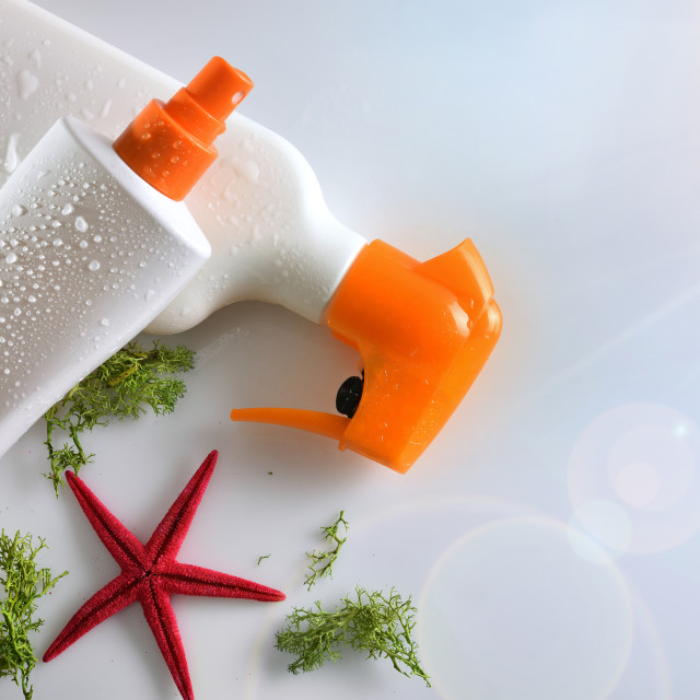 """Two sunscreen spray with starfish on glass table top view"" stock image"