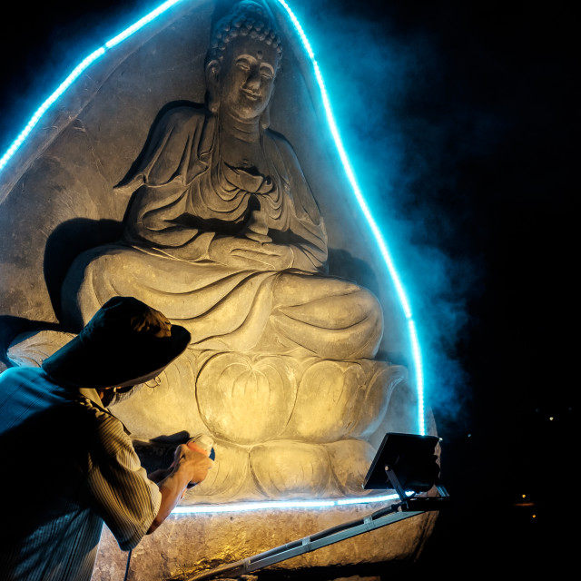 """""""A Man Sculpture a buddha statue in night-time."""" stock image"""