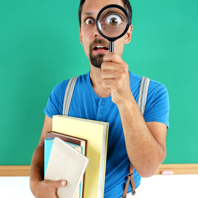 """""""Man open-eyed with magnifier, among the books."""" stock image"""