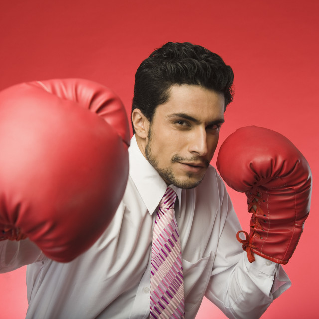 """Portrait of a businessman wearing boxing gloves"" stock image"