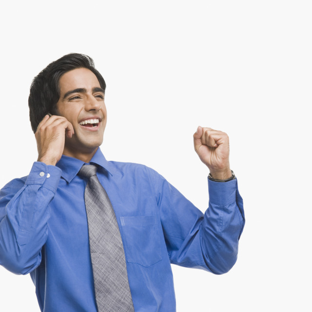 """Businessman raising fist while talking on a mobile phone"" stock image"
