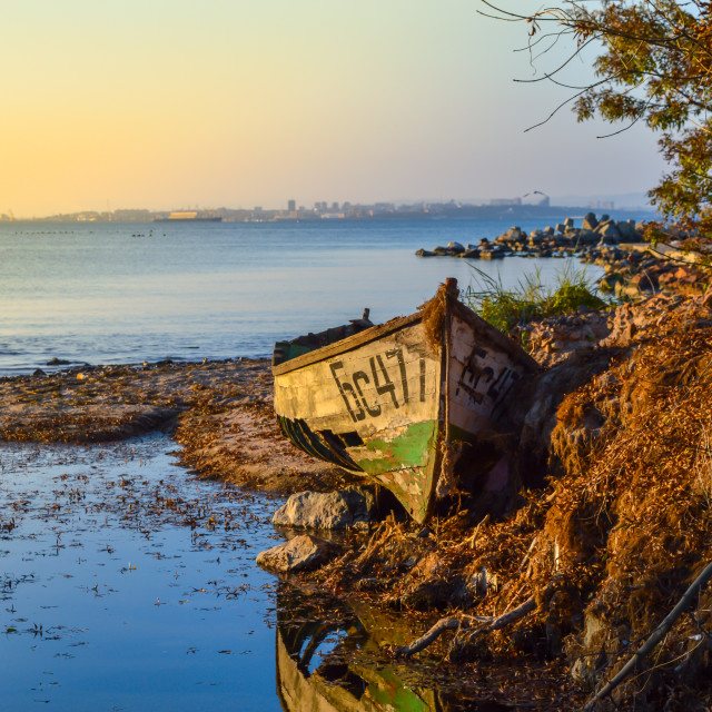 """Abandoned old boat on the beach at sunset"" stock image"