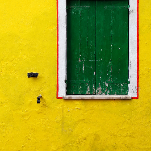 """A picturesque and bright yellow wall with a wooden green window"" stock image"