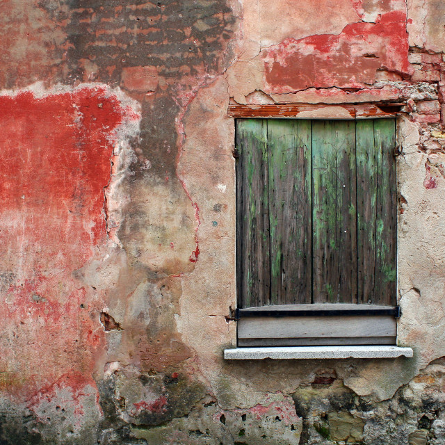 """An old red facade in ruins with a green wooden window"" stock image"