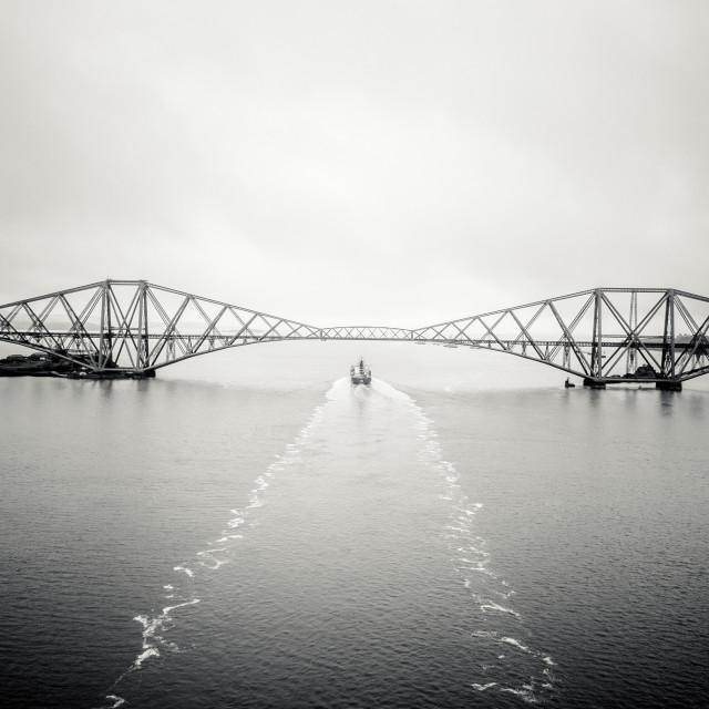 """Cargo Ship trails under the Forth Bridge Edinburgh"" stock image"