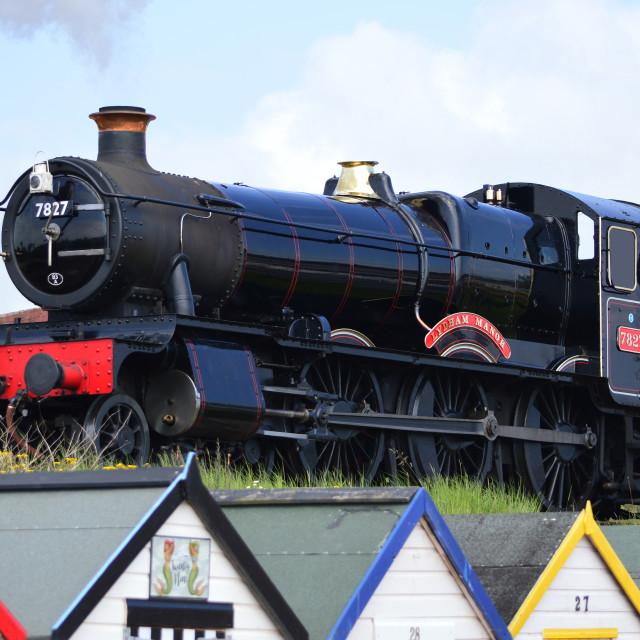 """Lydham Manor Steam Engine 7827 above beach huts, Goodrington Sands, Torbay, Devon, England"" stock image"