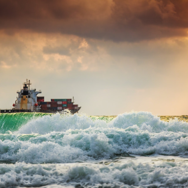 """Sun setting at the sea with sailing cargo ship, scenic view"" stock image"