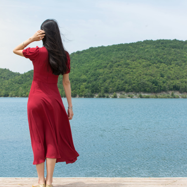 """""""Fashionable woman standing in front of a lake"""" stock image"""