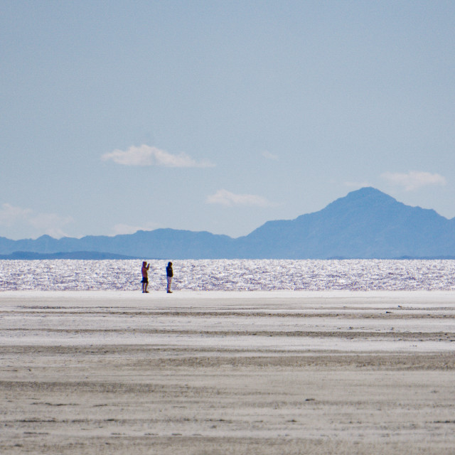 """""""2 people walk along the shore in the distance on the Great Salt Lake, near Spiral Jetty"""" stock image"""