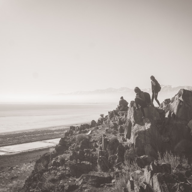 """""""a group of people scrambles along a rock outcropping with the Great Salt Lake in the background"""" stock image"""