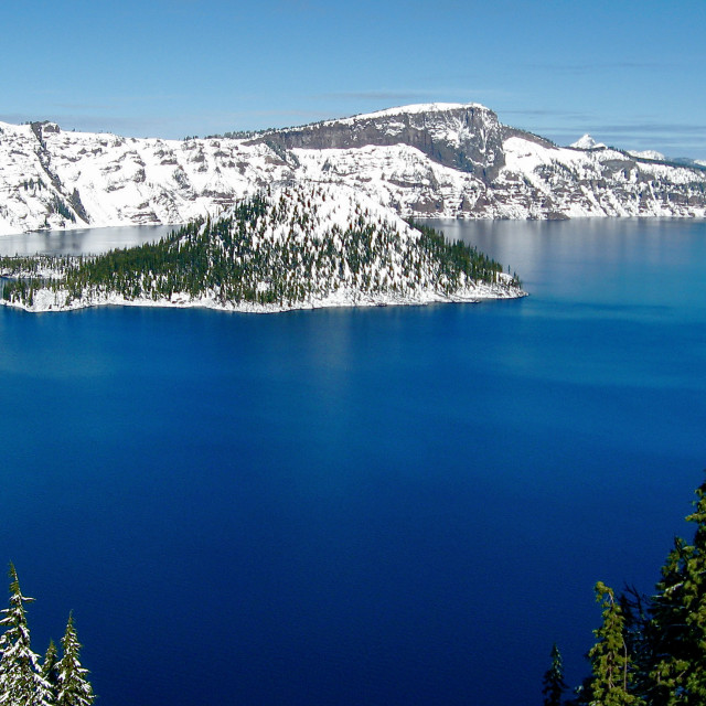 """""""A view of the island in Crater Lake with snow on the mountains"""" stock image"""