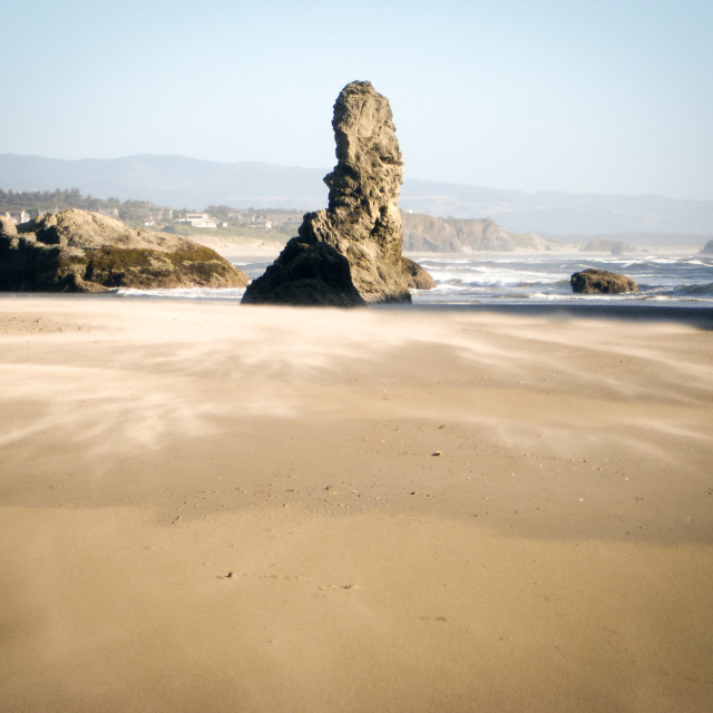 """""""The wind blows the sand against the rocks and the waves on the Oregon Coast"""" stock image"""