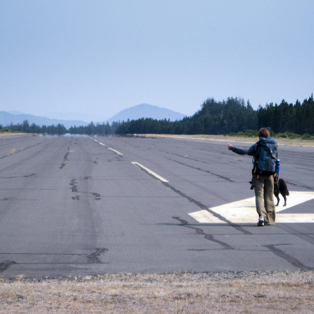 """""""A woman tries to hitchhike on a runway with mountains in the background"""" stock image"""