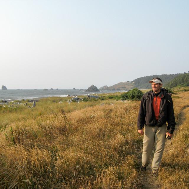 """a man hikes along a coastal dune"" stock image"