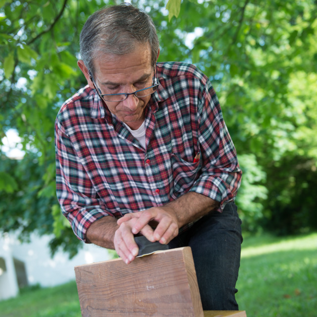 """""""Using a sanding block on the edge of a board"""" stock image"""