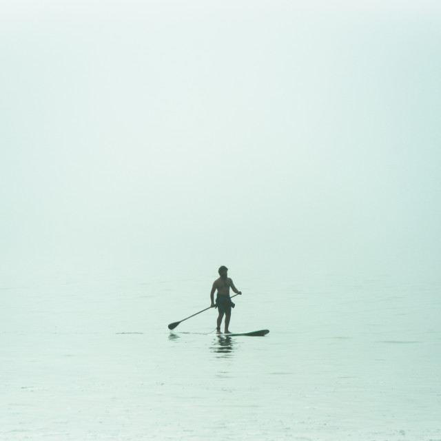 """""""A young man paddles his stand-up surfboard in the sea offshore."""" stock image"""