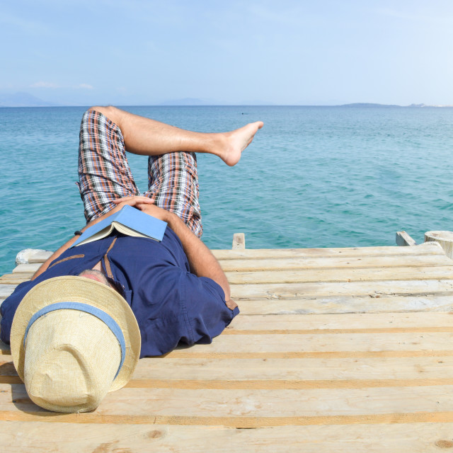 """Man lying on the dock with a book"" stock image"