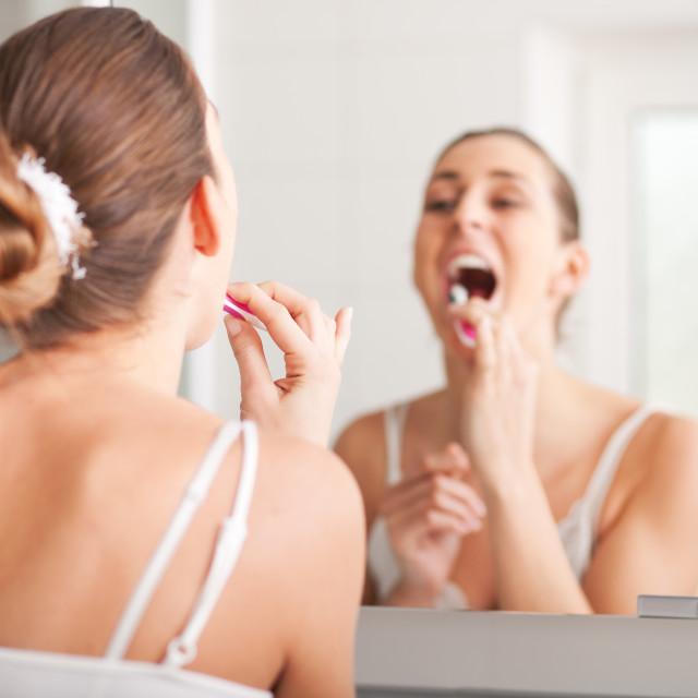 """""""Young woman brushing teeth at wash bowl"""" stock image"""