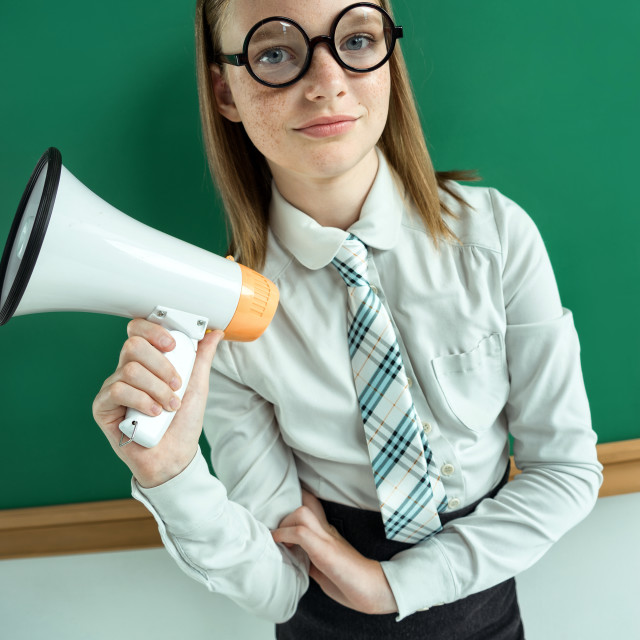 """Student standing near blackboard with a megaphone."" stock image"