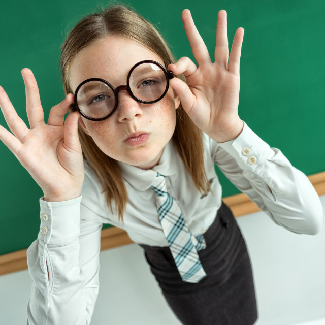 """Student with an intelligent expression, correcting glasses. Photo of teen near blackboard, education concept"" stock image"