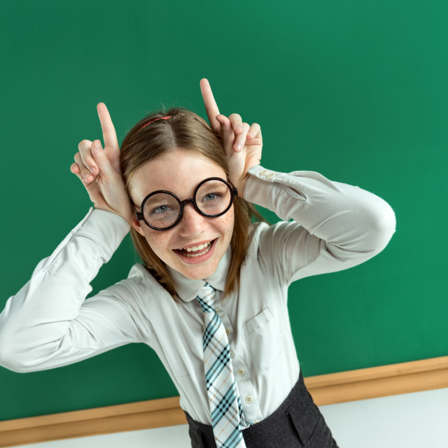 """Naughty pupil making sassy funny expressions, showing horns her hands. Photo of teen school girl wearing glasses, creative concept with Back to school theme"" stock image"