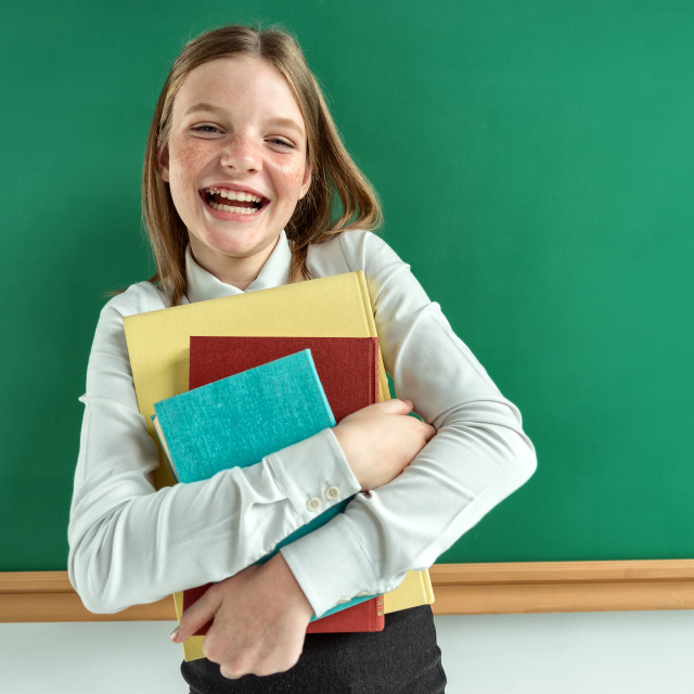 """Happy schoolgirl likes read a books."" stock image"