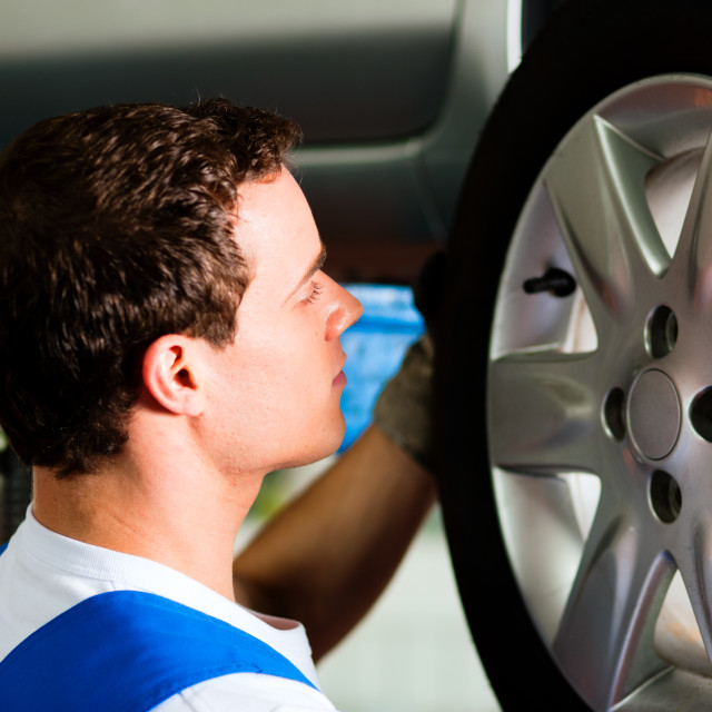"""Car mechanic in workshop changing tire"" stock image"